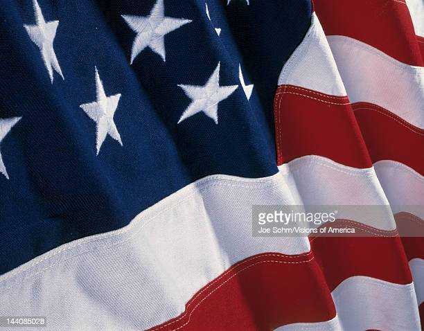 This is an American flag with waves folding over the blue field of stars and red and white stripes