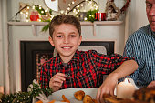 Happy little boy is smiling for the camera while sitting at the table for christmas dinner.