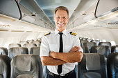 Confident male pilot in uniform keeping arms crossed and smiling while standing inside of the airplane