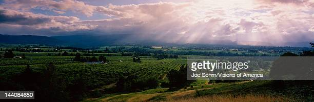 This is near the Hood River It is a green valley with houses and farms scattered throughout The sun is projecting god rays down over the valley...