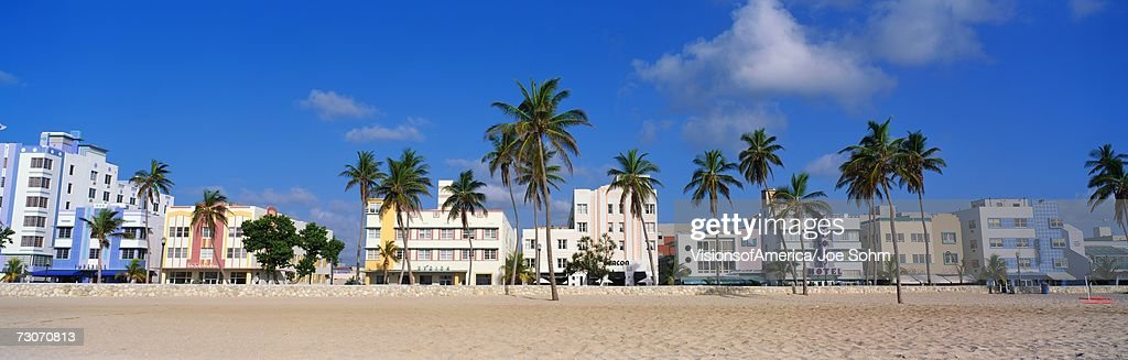 This is the art deco district of South Beach Miami. The buildings are painted in pastel colors surrounded by tropical palm trees. : Stock Photo