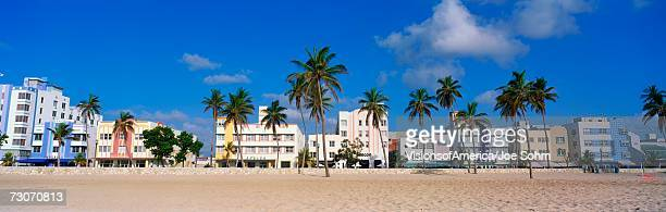 This is the art deco district of South Beach Miami. The buildings are painted in pastel colors surrounded by tropical palm trees.