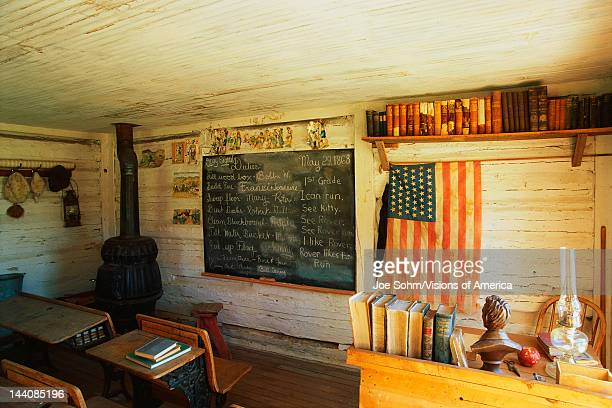 This is the interior of a one room school house It was the first school in Montana from 1868 There is a black chalkboard and American flag hanging on...