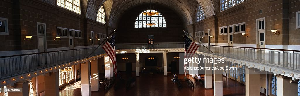 This is the interior of the Great Hall at Ellis Island which signifies immigration to the United States.  There are two American flags flying posted at the center of the walls. : Stock Photo