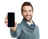 Studio portrait of a handsome businessman showing a phone with a blank screen against a white background