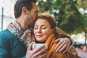 Cute married couple is sitting and hugging outdoors. They are warming up by blanket and hot tea. Lovers are smiling happily