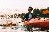 Handsome young smiling man splashing water while kayaking on river