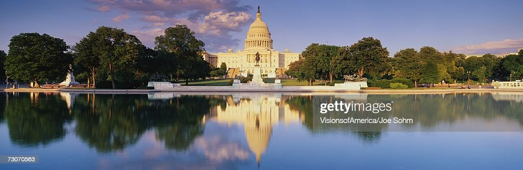 'This is the U.S. Capitol showing the West side view at sunset. The Capitol is in front of the reflecting pool, showing a reflection of itself in the pool. The Capitol is surrounded by green trees and a blue sky with a public statue in front of it.' : Stock Photo