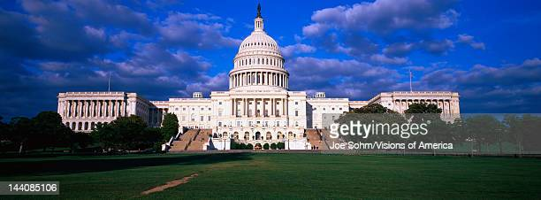 This is the West view of the US Capitol at sunset It is surrounded by a lawn in front with a blue sky and white puffy clouds