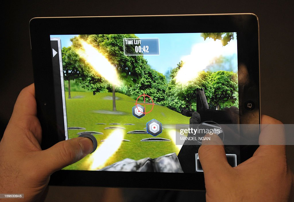 This January 15, 2013 photo taken in Washington, DC, shows a man playing the newly released National Rifle Association(NRA) iPhone/iPad app, 'NRA: Practice Range.' The new app was released January 14, by the nation's largest gun-industry lobby. The game gives users choices of several weapons and targets to shoot at, simulating firing at a gun range. AFP PHOTO/Mandel NGAN