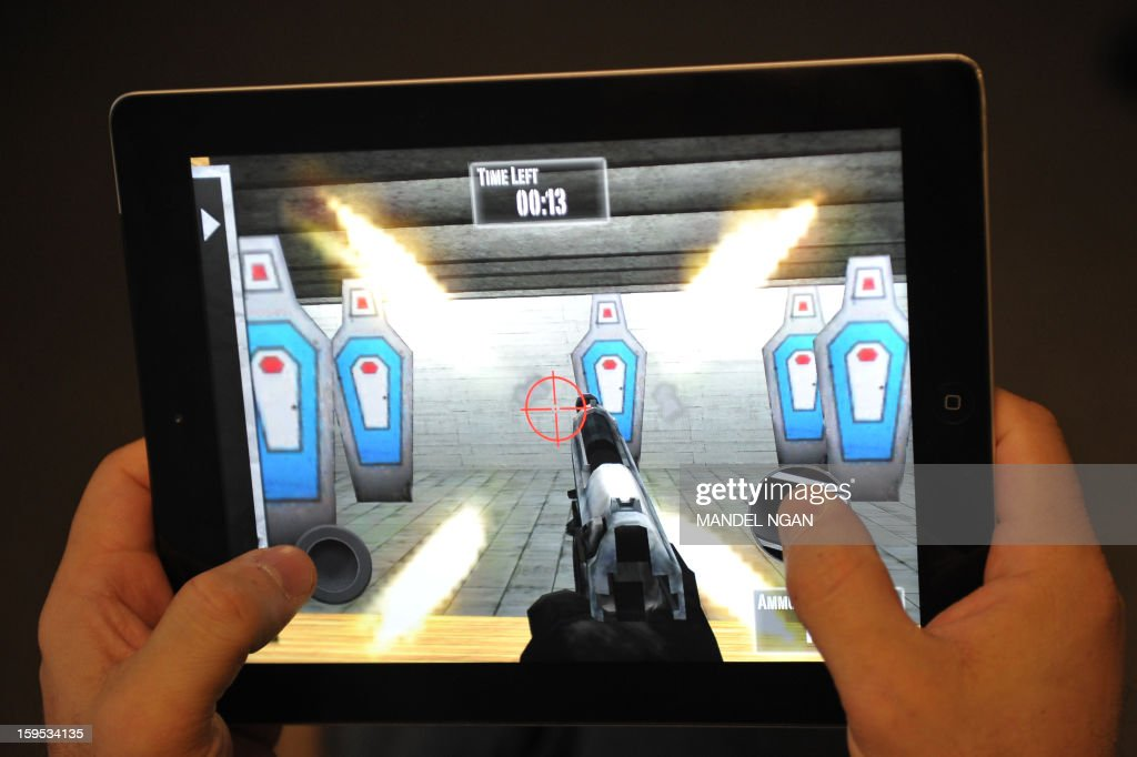 This January 15, 2013 photo taken in Washington, DC, shows a man playing the newly released National Rifle Association(NRA) iPhone/iPad app, 'NRA: Practice Range.' The new app was released January 14, by the nation's largest gun-industry lobby. The game gives users choices of several types of weapons and targets to shoot at, simulating firing at a gun range. AFP PHOTO/Mandel NGAN