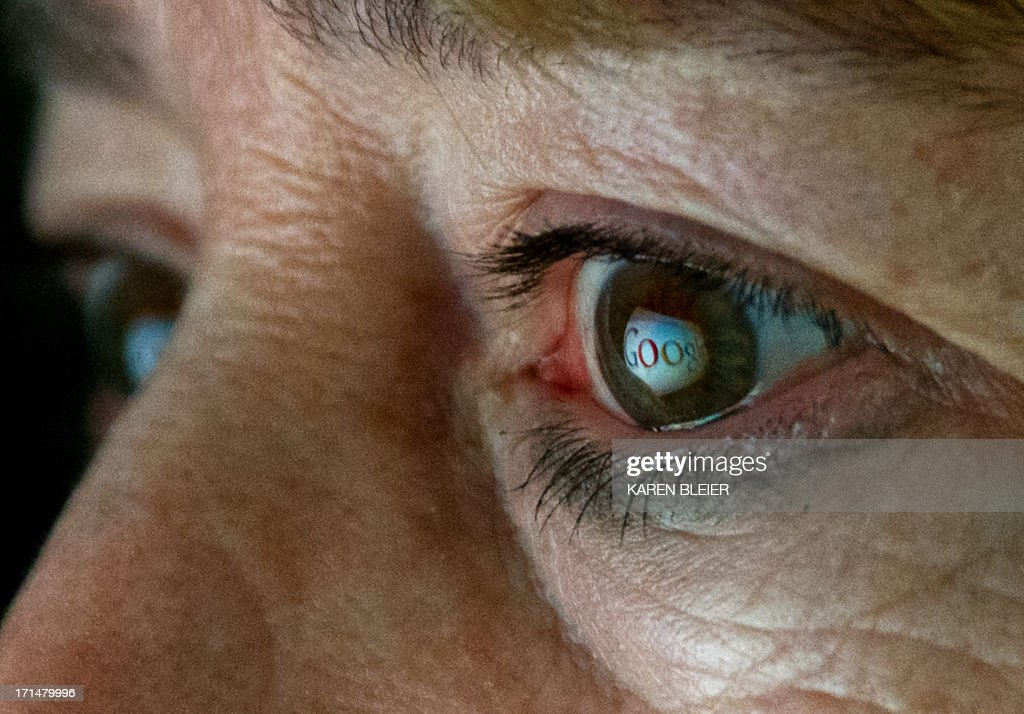 This June 25, 2013 photo illustration shows the Internet search giant Google logo reflected in a woman's eye. AFP PHOTO / Karen BLEIER