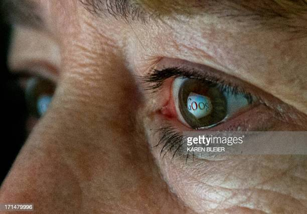 This June 25 2013 photo illustration shows the Internet search giant Google logo reflected in a woman's eye AFP PHOTO / Karen BLEIER