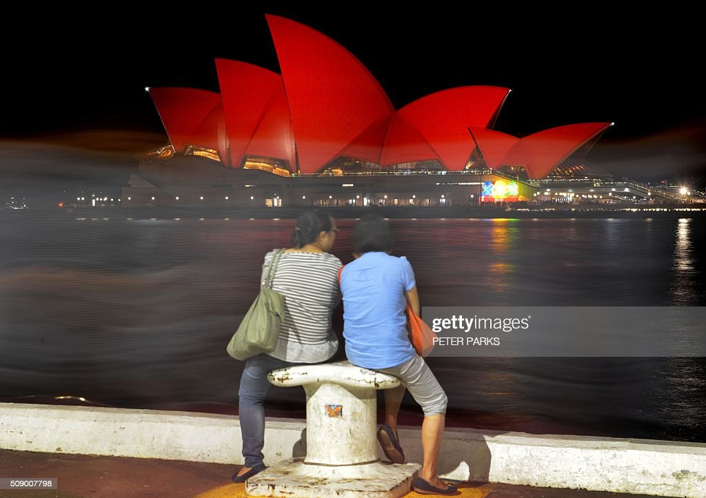 This long exposure photograph shows Chinese tourists sitting and viewing the Sydney Opera House which is lit up red to welcome in the Lunar New Year in Sydney on February 8, 2016. The Lunar New Year of the Monkey begins on February 8. AFP PHOTO / Peter PARKS / AFP / PETER PARKS