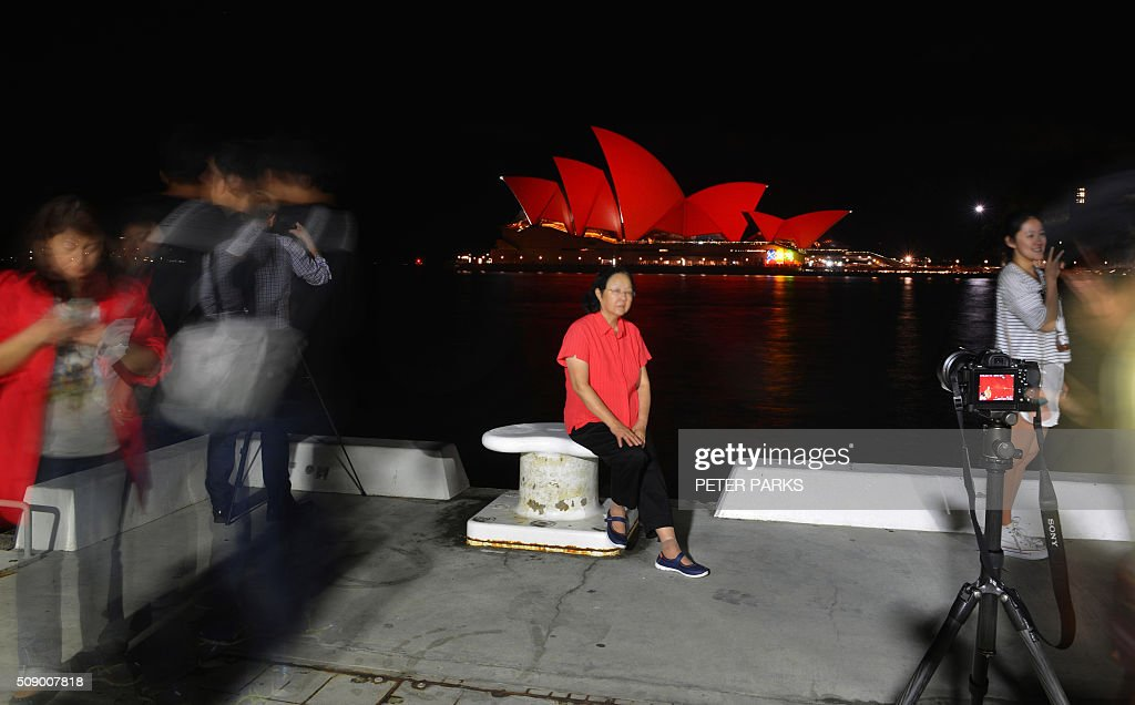 This long exposure photograph shows Chinese tourists taking photographs in front of the Sydney Opera House which is lit up red to welcome in the Lunar New Year in Sydney on February 8, 2016. The Lunar New Year of the Monkey begins on February 8. AFP PHOTO / Peter PARKS / AFP / PETER PARKS