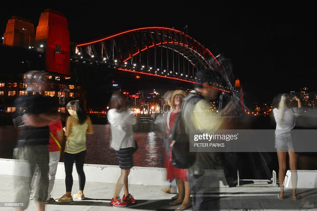 This long exposure photograph shows Chinese tourists taking photos in front of Sydney Harbour Bridge which is lit up red to welcome in the Lunar New Year in Sydney on February 8, 2016. The Lunar New Year of the Monkey begins on February 8. AFP PHOTO / Peter PARKS / AFP / PETER PARKS