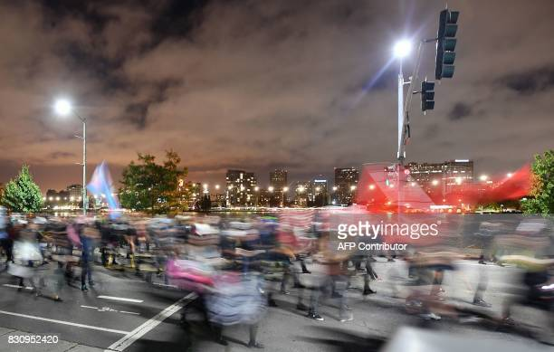 This long exposure photograph shows protesters marching against racism along a street in Oakland California on August 12 2017 Protesters marched on...