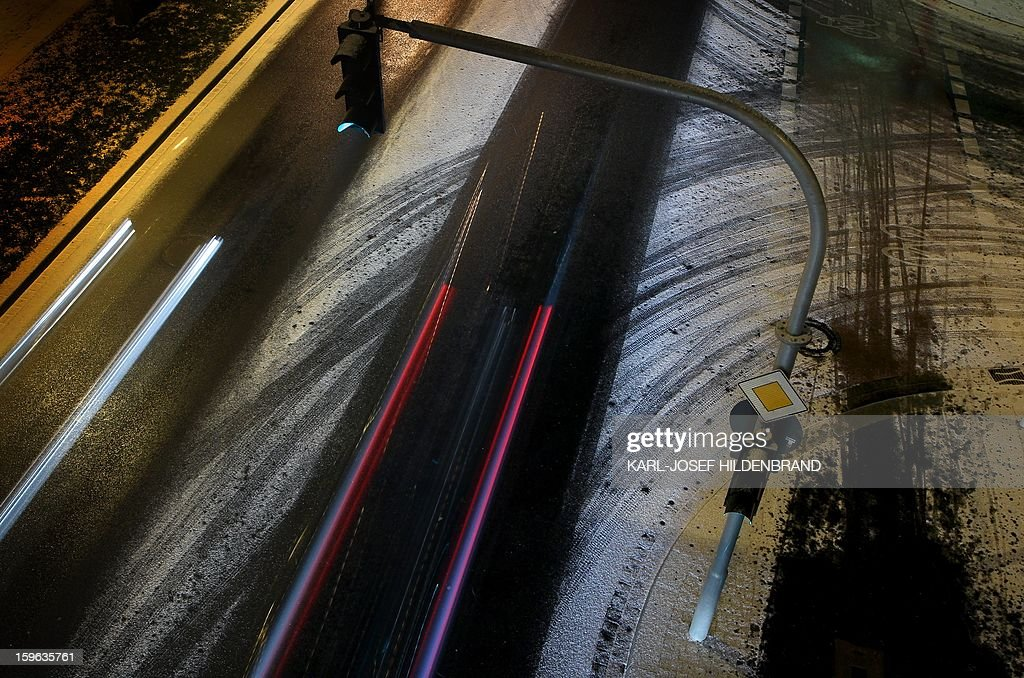 This long time exposure photo shows a car driving on a street that is slightly covered with snow in Wuerzburg, southern Germany, on January 15, 2013.
