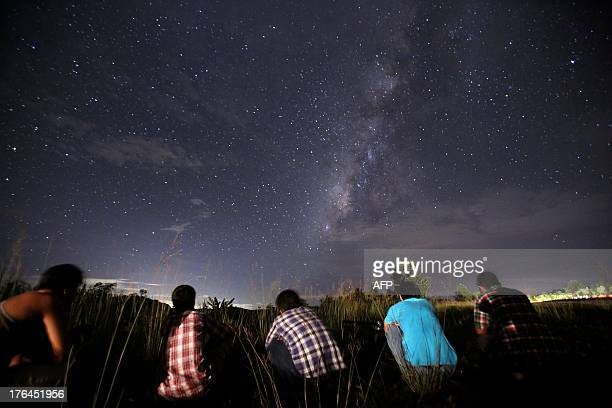 This longexposure photograph taken on August 12 2013 shows people watching for the Perseid meteor shower in the night sky near Yangon The meteor...
