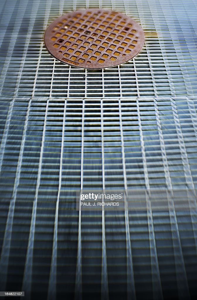 This March 28, 2013 photo illustration shot with a perspective control lens shows a rusty man hole cover surrounded by a sidewalk grate on the sidewalks of Washington, DC. The grates are famous for breaking high heeled shoes. The AFP PHOTO/Paul J. Richards
