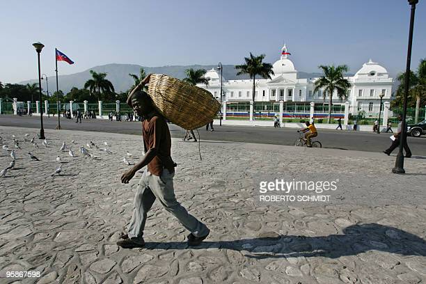 This May 12 2006 file photo shows Jean Paul Billy a Haitian man who makes a living by selling bread in the streets carrying two empty baskets as he...