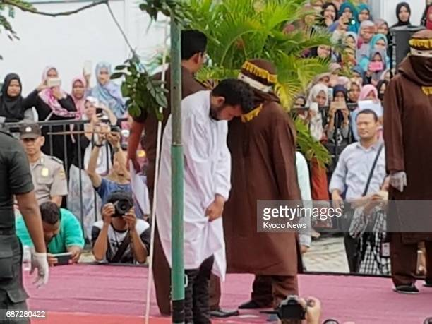 This May 23 photo shows one of two men who was punished by caning with 83 lashes each in front of the public in Indonesia's northernmost Aceh...