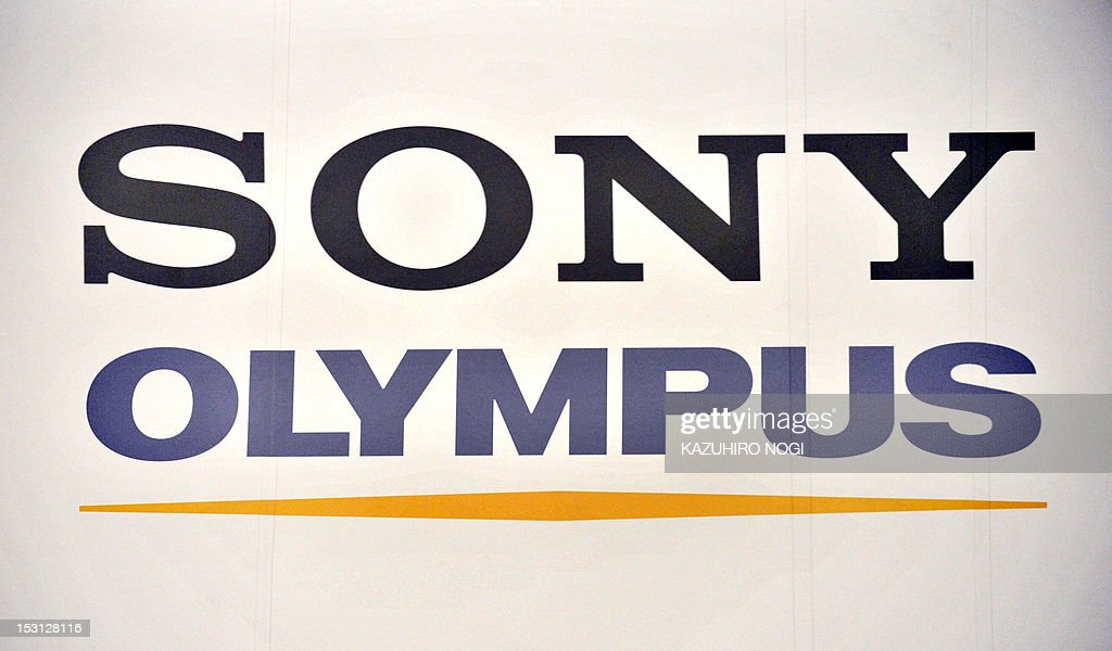 This multiple exposure shows logo's of Japan's Sony Corporation (top) and Olympus Corporation (bottom) displayed at a joint press conference in Tokyo on October 1, 2012. Olympus and Sony announced that the two companies have entered into a business alliance agreement and a capital alliance agreement through a third-party allotment of Olympus's common shares to Sony. AFP PHOTO / KAZUHIRO NOGI