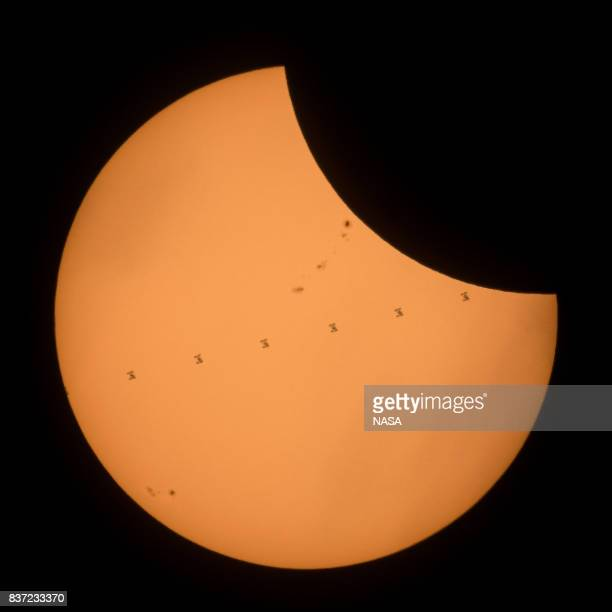 This NASA handout composite image shows the International Space Station with a crew of six onboard as it transits the Sun at roughly five miles per...