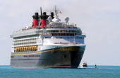 This November 29 2009 photo shows passengers lining the rail as the Disney cruise ship Magic enters the harbor in Key West Florida AFP PHOTO/Karen...