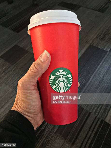 This November 9 2015 photo shows a consumer holding the 2015 Starbucks holiday cup in Washington DC The unadorned red cup which debuted November 1...
