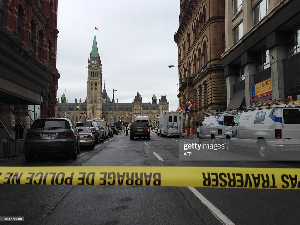 This October 16 2013 photo shows the parliament building in Ottawa Canada from behind a police barrier after it was locked down Federal police swept...
