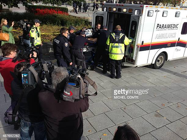 This October 22 2014 photo shows police and medical personell moving a wounded person into an ambulance at the scene of a shooting at the National...