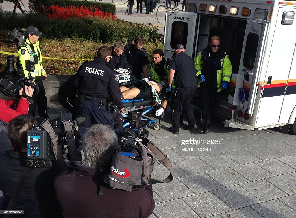 This October 22 2014 photo shows police and medical personell moving a wounded Canadian soldier into an ambulance at the scene of a shooting at the...