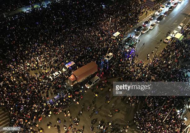 This overhead view shows emergency vehicles amongst the crowd after a stampede by new year's revellers in Shanghai's historic riverfront in Shanghai...