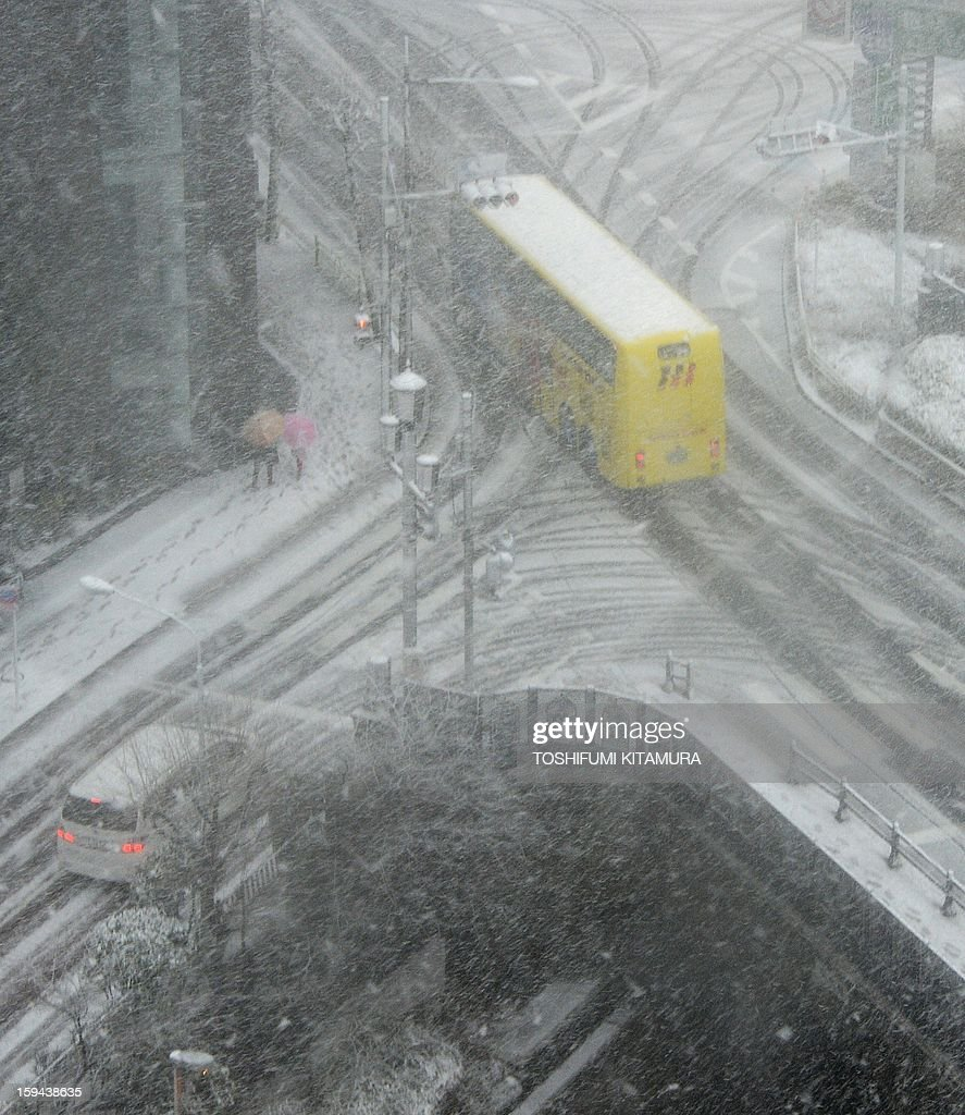 This overhead view shows vehicles slowly making their way through the snow-covered streets near the Ginza shopping district in Tokyo on January 14, 2013. A storm system grasped central Japan on January 14, causing heavy snow fall around the Japanese capital.