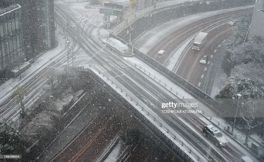 This overhead view shows vehicles slowly making their way through the snow-covered streets of Tokyo on January 14, 2013. A storm system grasped central Japan on January 14, causing heavy snow fall around the Japanese capital.