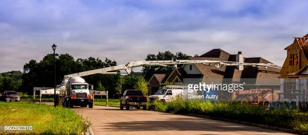 Waco, TX, USA - June 1, 2016: This panorama shows a white concrete delivery vehicle pumps concrete through an extended arm to construct a foundation of a residential building.