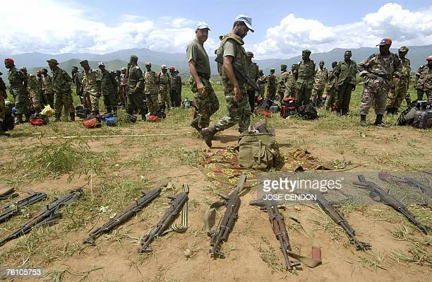 This photo dated 15 December 2005 shows UN peacekeeping forces soldiers inspecting FDLR weapons in front of miliatiamen in the demobilization camp of...