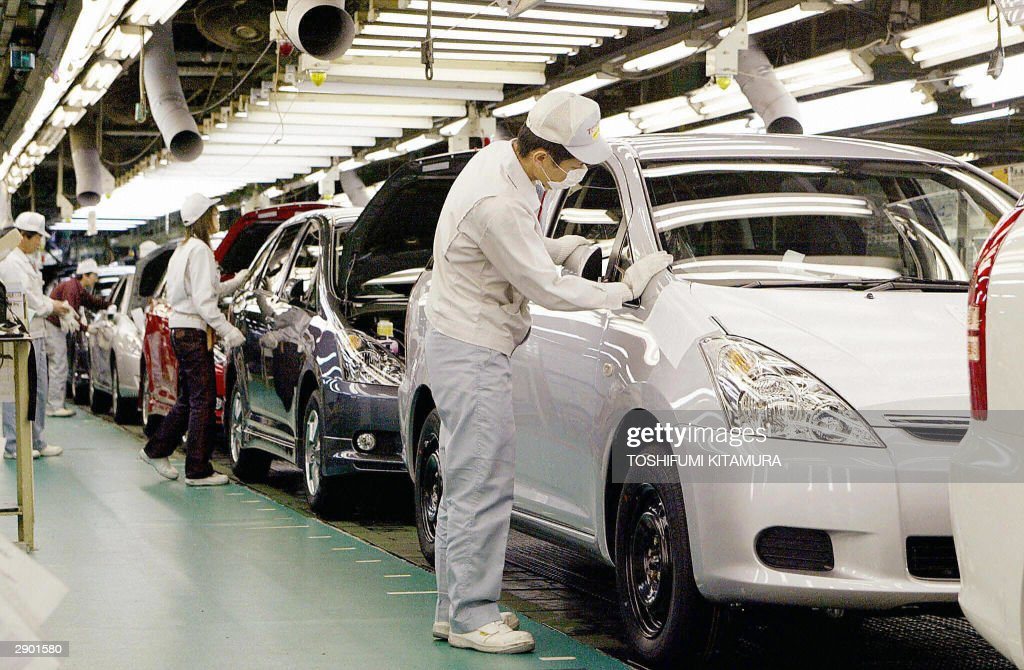 This photo dated 20 February 2003 shows workers putting parts onto Toyota Motor's new vehicle 'Wish' on the assembly line of the company's Tsutsumi...