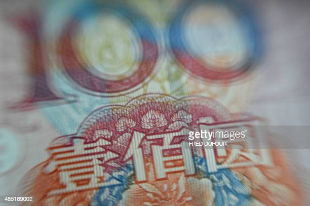 This photo illustration shows a Chinese 100yuan note in Beijing on August 25 2015 China's central bank on August 25 cut its benchmark interest rates...