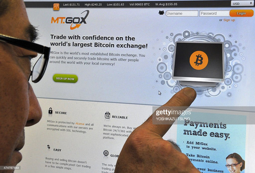 This photo illustration shows a man looking at the bitcoin exchange website of MtGox in Tokyo on February 25, 2014. The website of Tokyo-based bitcoin exchange MtGox went down on February 25, after the value of the virtual unit sank to about a quarter of that on other platforms and Japanese regulators said they were unable to step in. AFP PHOTO / Yoshikazu TSUNO