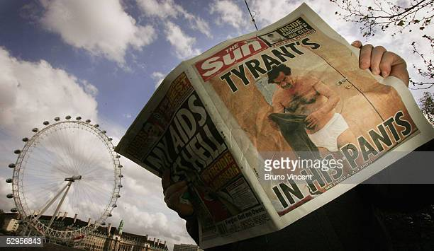 This photo illustration shows a man reading a copy of The Sun newspaper with an image of former President Saddam Hussein in his underwear May 20 2005...