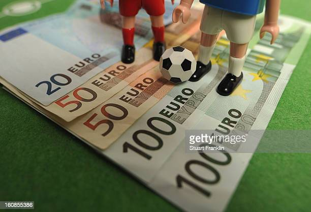 This photo illustration shows Euro bank notes and a table soccer game on February 6 2013 in Hamburg Germany Europol have uncovered evidence that...