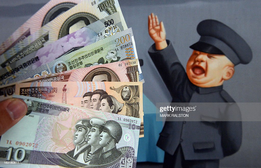 This photo illustration shows North Korean currency purchased at a Chinese border town and displayed in front of a painting in Beijing on March 6, 2013. The United States and China called on the UN Security Council to sanction North Korean diplomats and 'illicit' cash transfers to step up pressure on Pyongyang's nuclear program. AFP PHOTO/Mark RALSTON