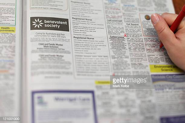 This photo illustration shows someone marking a newspaper employment section on August 13 2011 in Sydney Australia News the unemployment rate rose...