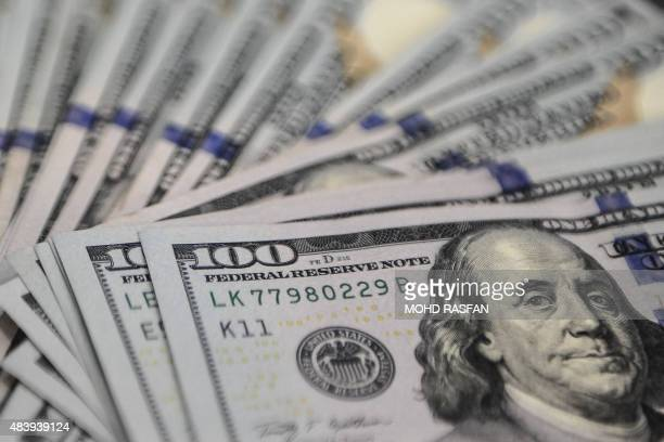 This photo illustration shows US dollar notes at a foreign currency dealer in Ampang on August 14 2015 Malaysia's ringgit currency slid past 40 to...