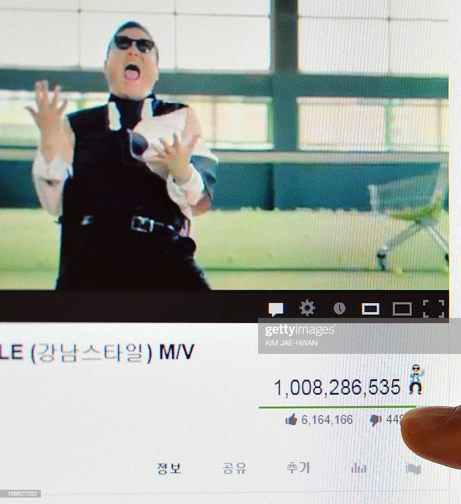 This photo illustration taken in Seoul on December 21, 2012 shows a person's finger pointing at a counter (bottom R) on a computer screen showing the number of times that viewers have watched South Korean rapper Psy's video 'Gangnam Style' (top) on YouTube, confirming its status as the most viewed video in the site's history. Psy's 'Gangnam Style' became the first video to hit a billion views on YouTube on December 21, marking a fresh milestone in the global craze for the South Korean rapper and his horse-riding dance.