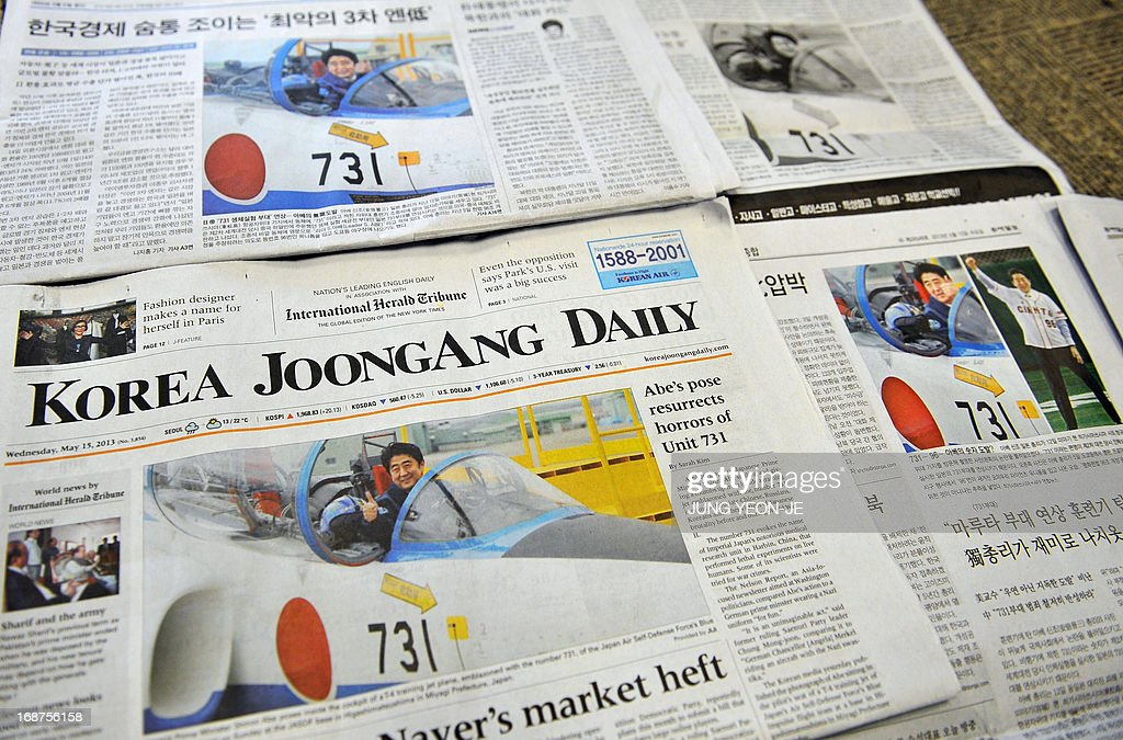 This photo illustration taken in Seoul on May 15, 2013 shows South Korean newspaper front pages with coverage of Japanese Prime Minister Shinzo Abe seated inside a military jet trainer on May 12. South Korean newspapers splashed a photo of Japanese Prime Minister Shinzo Abe in a military jet trainer on their front pages on May 15, 2013, saying it was a reminder of Japan's colonial-era atrocities. The picture in question showed a smiling Abe giving a thumbs-up while sitting in the cockpit of an air force T-4 training jet emblazoned with the number 731.