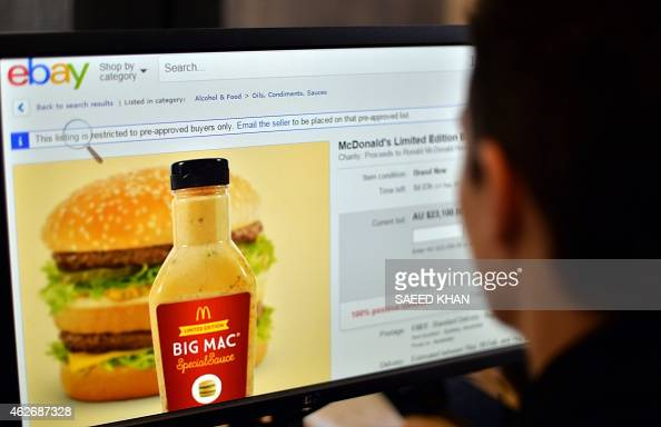 This photo illustration taken on February 3 2015 shows a woman in Sydney looking at a webpage of eBay offering bids for fastfood giant McDonald's Big...