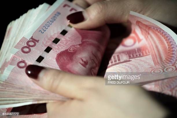 This photo illustration taken on February 9 2017 shows Chinese 100 yuan notes in Beijing China's exports soared a forecastbeating 79 percent in...